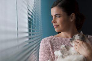mujer con gato mirando por la ventana