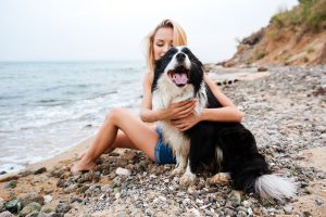 Happy pretty young woman hugging her dog on the beach